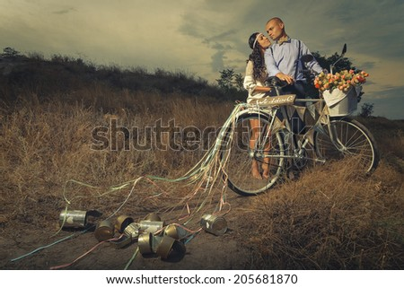 Groom and bride on a bicycle with just married sign and cans attached - stock photo