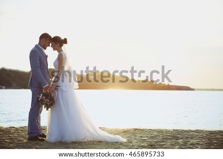 Groom and bride on sunset background