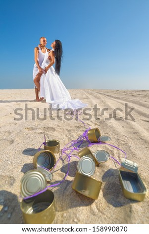 Groom and bride on the beach with cans attached - stock photo