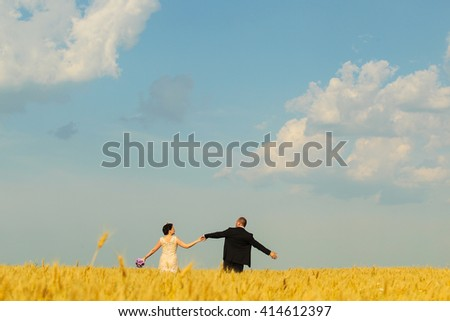 groom and bride on the field on their wedding day