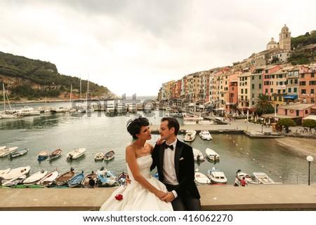 groom and bride posing in pier - stock photo