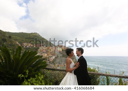 groom and bride posing near the sea