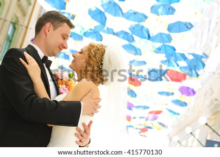 groom and bride posing under a roof made with umbrellas - stock photo