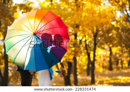 Groom and bride's shadows kissing behind an umbrella outdoors in autumn - stock photo