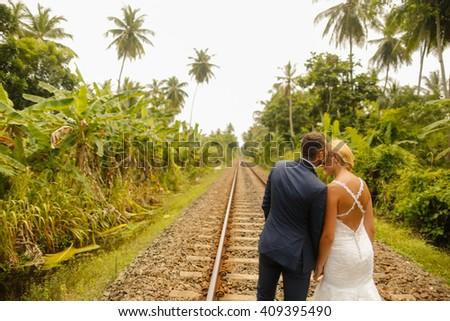 groom and bride walking on railway - stock photo