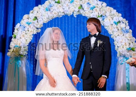 groom and bride with a bouquet, posing in their wedding day. Enjoy a moment of happiness and love. - stock photo