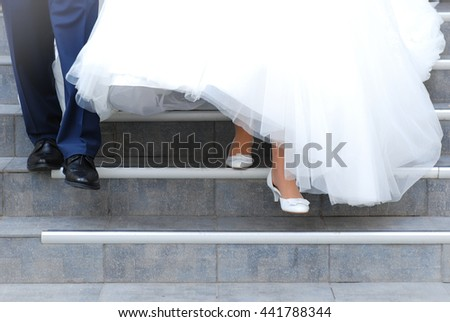 Groom and bride (young couple) are going down the stairs - stock photo