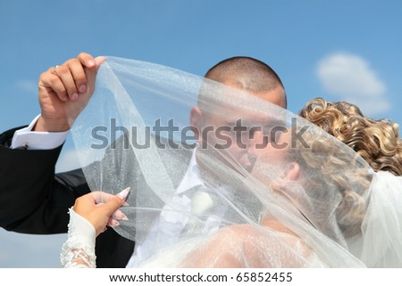 groom and the bride passionately kiss under a veil against the blue sky in a sunny day - stock photo