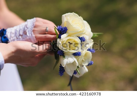 Groom and the bride with a bouquet of roses. Bride with groom holding wedding bouquet at ceremony. Wasp, bee on a rose bud. - stock photo