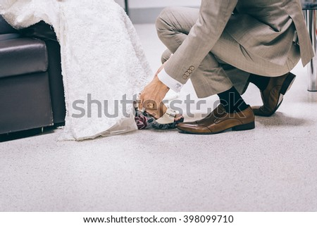 Groom assisting bride putting on her shoes