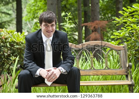 Groom at wedding sitting on a bench - stock photo