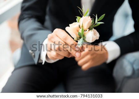 Groom attach flowers to the suit
