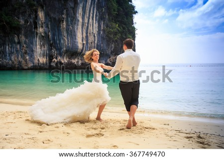groom blonde curly bride in fluffy wedding dress join hands swing on edge of sand beach against azure sea green cliff - stock photo