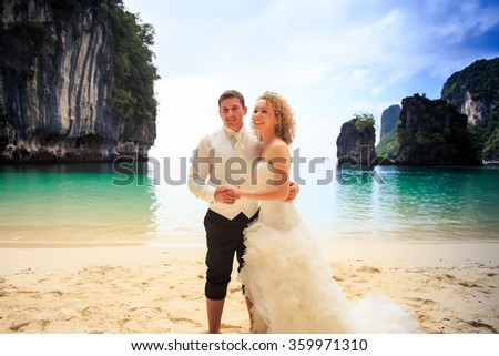 groom blonde curly bride in fluffy wedding dress stand closely join hands on sand beach against azure sea green cliff - stock photo
