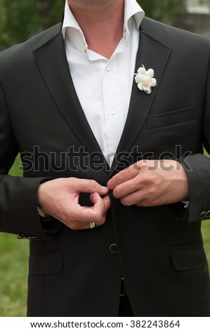 Groom buttons black jacket with white flower - stock photo