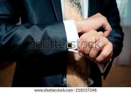 Groom buttons on his shirt cuffs