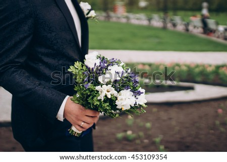 groom carries a bouquet of flowers, side view