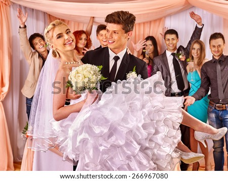 Groom  carries bride on his hands  at wedding. Flower bouquet. - stock photo