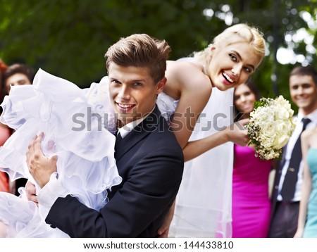 Groom carries his bride over shoulder. Outdoor. - stock photo