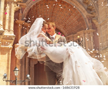 groom carrying bride near church - stock photo