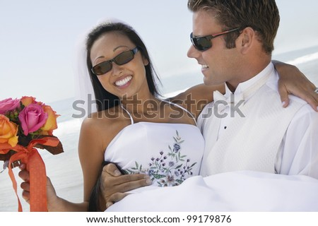 Groom Carrying Bride on Beach