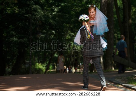 groom carrying the bride on the background park - stock photo