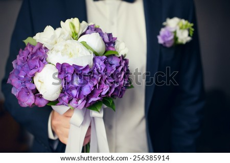 Groom close up , focus on wedding  bouquet - stock photo