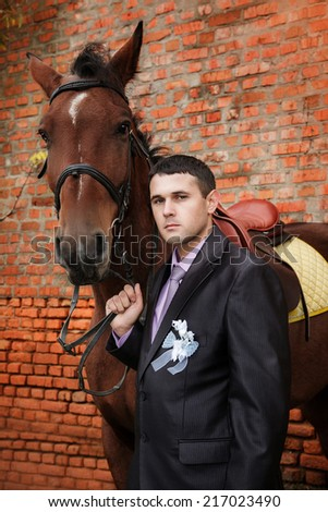 groom  during walk in their wedding day against a brown horse and old brick wall - stock photo