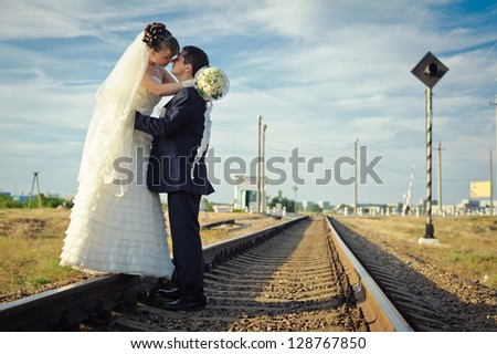 groom embraces the bride on rails. Happy young bride and groom on their wedding day. Wedding couple - new family! wedding dress. Bridal wedding bouquet of flowers - stock photo