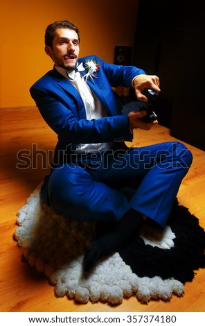 Groom game computer game while sitting on the carpet with yin yang simbol - stock photo