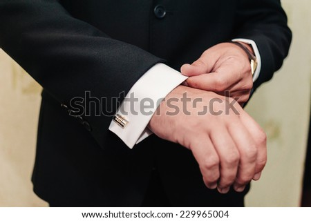 GROOM GETTING READY. A groom putting on cuff-links as he gets dressed in formal wear