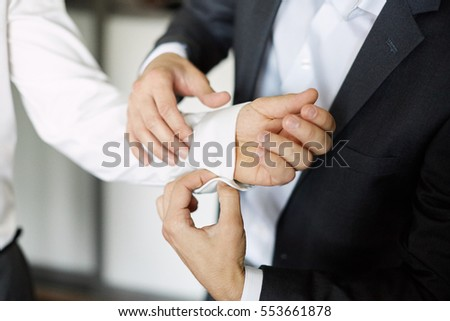 groom getting ready dressed in the morning. buttons in white shirt