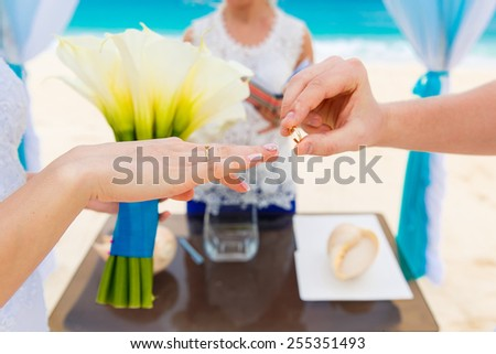 Groom giving an engagement ring to his bride under the arch decorated with flowers on the sandy beach. Wedding ceremony on a tropical beach in blue. Wedding and honeymoon concept.