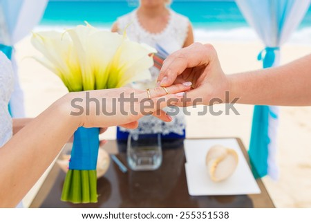 Groom giving an engagement ring to his bride under the arch decorated with flowers on the sandy beach. Wedding ceremony on a tropical beach in blue. Wedding and honeymoon concept. - stock photo