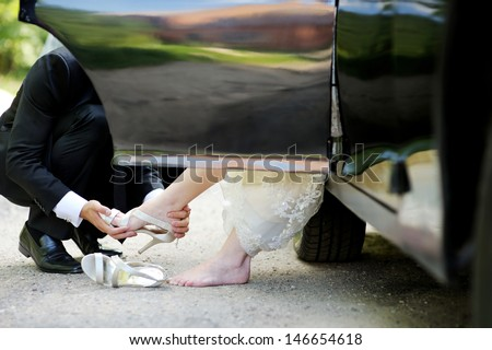Groom helping his bride to put her shoes on - stock photo