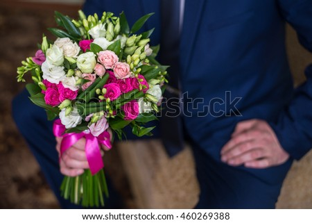 groom hold wedding bouquet in his hand