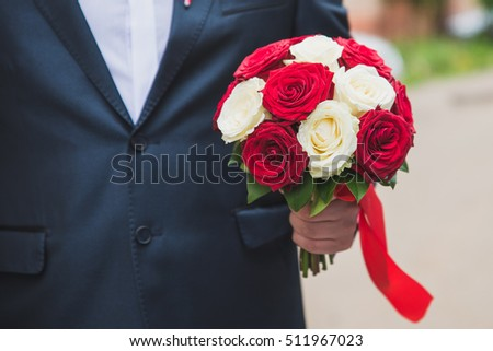 groom holding a bouquet of white daisies, flowers in male hands