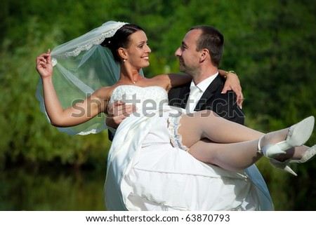 groom holding a bride up in his hands