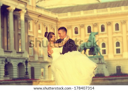 Groom holding bride in his arms - stock photo