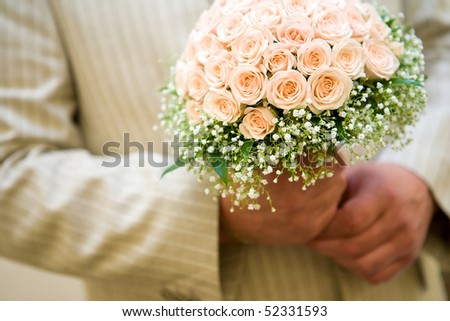 Groom holding Bride's bouquet close up