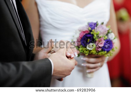 Groom holding bride's hand during the wedding ceremony - stock photo