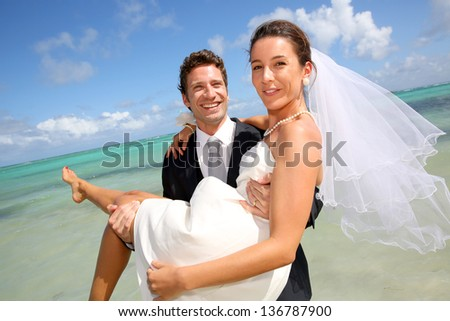 Groom holding his bride by the Caribbean sea