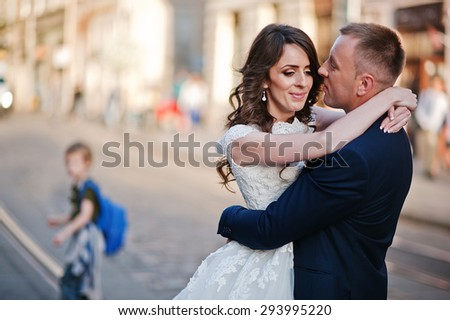 Groom holding on hands his bride on background old city