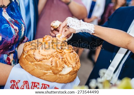 Groom holding slice of traditional wedding round loaf and bride salt it - stock photo