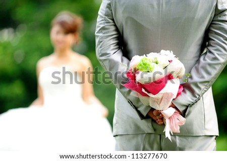 Groom holding wedding flower bouquet - stock photo