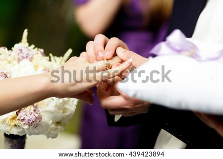Groom holds bride arm tenderly while he puts a wedding ring on her finger - stock photo