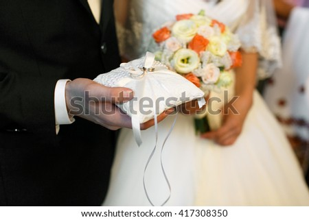 Groom holds in his arm wedding rings - stock photo