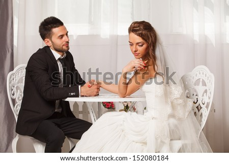 groom holds the hand of a shy bride - stock photo