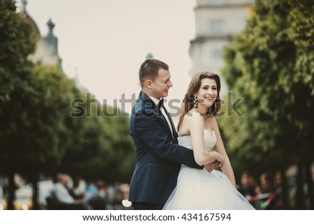 Groom hugs a smiling bride from behind standing on the green lane - stock photo