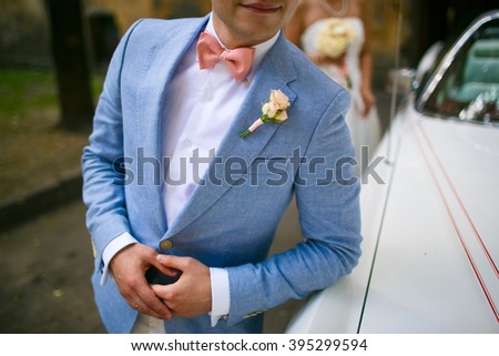 Groom in a blue coat with pink butterfly standing at the car. On the jacket a boutonniere of roses. In the background the bride in a white dress with a bouquet - stock photo
